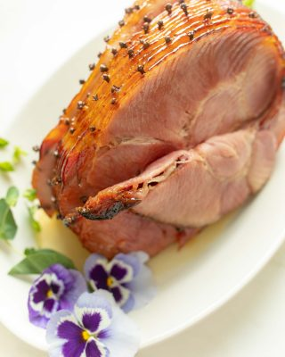 honey glazed ham studded with cloves on platter with pansies for garnish