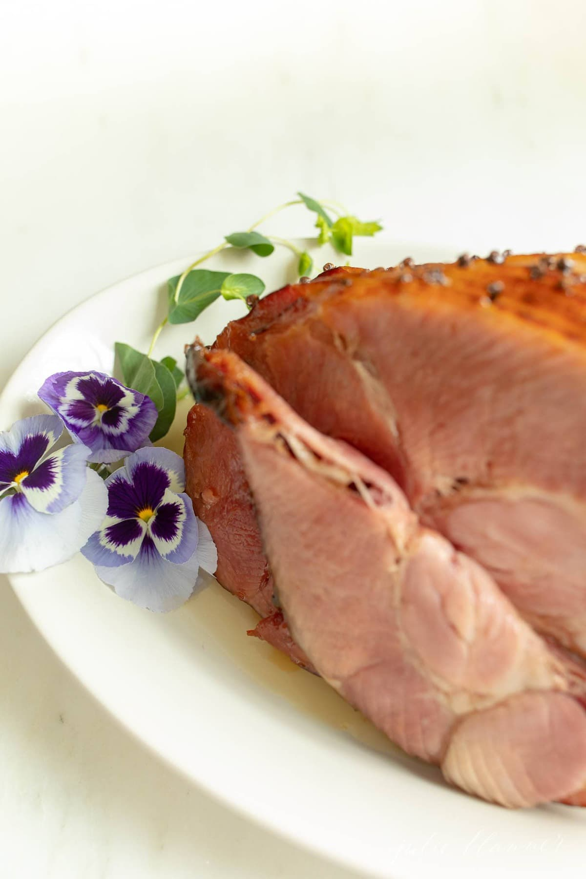 A sliced honey ham on a white platter, garnished with fresh flowers