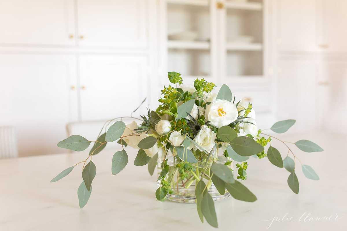 White Ranunculus Centerpiece in glass vase in a white kitchen