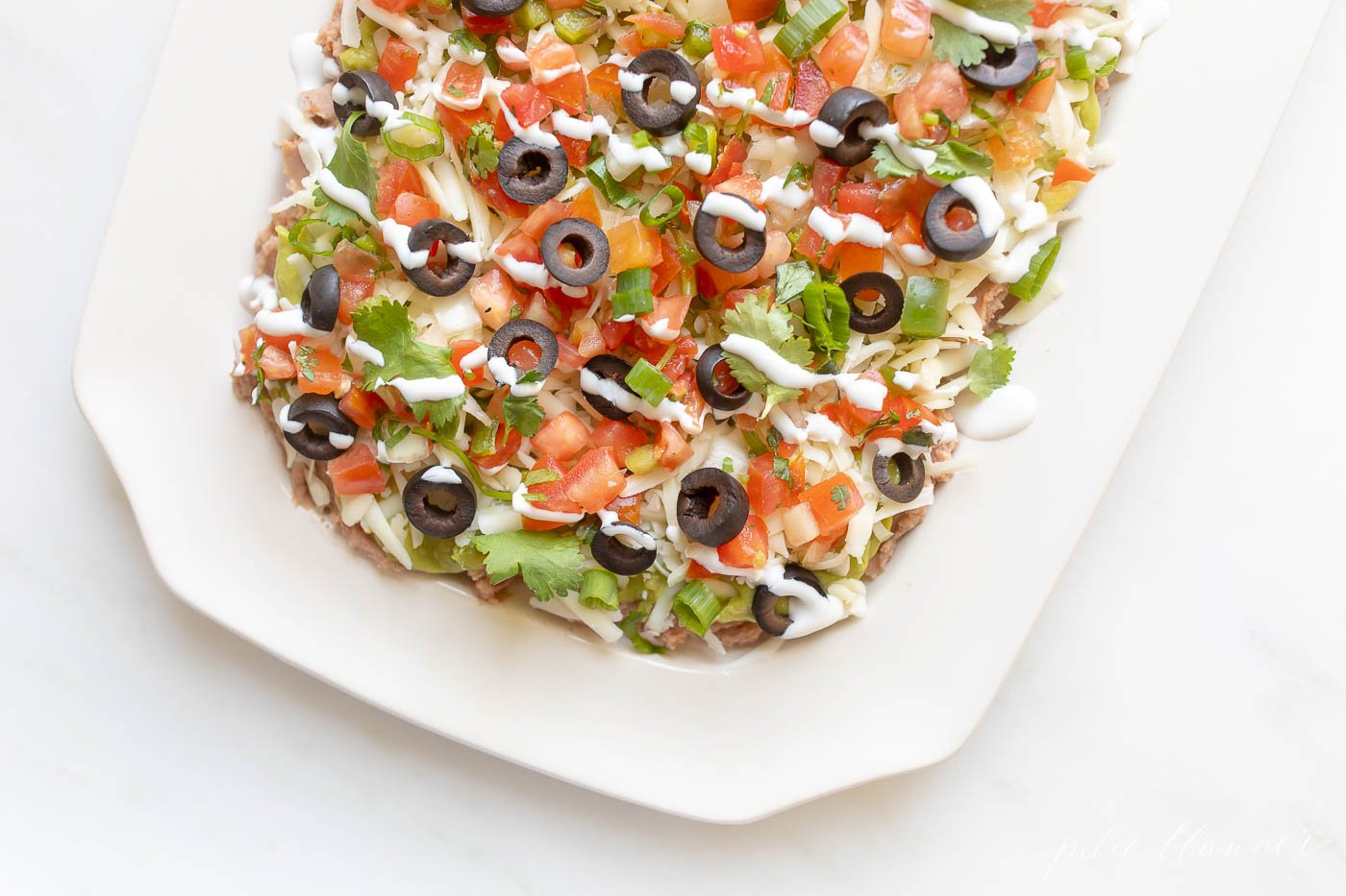 Close-up of layered Mexican dip on a serving platter