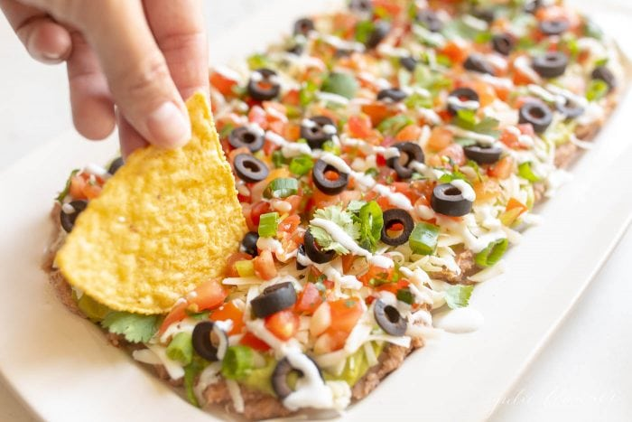 7 layer dip in a white dish, tortilla chips being dipped in.
