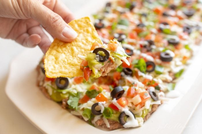 A hand dipping into Mexican layered dip