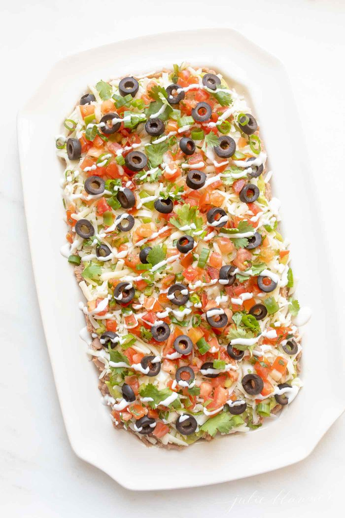 A classic Mexican 7 layer dip on a white serving platter