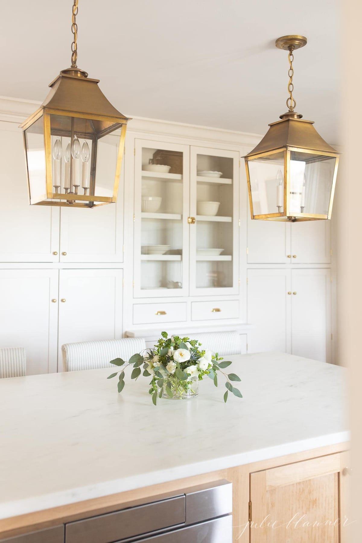 White kitchen with hanging lanterns, white ranunculus flower centerpiece on island.
