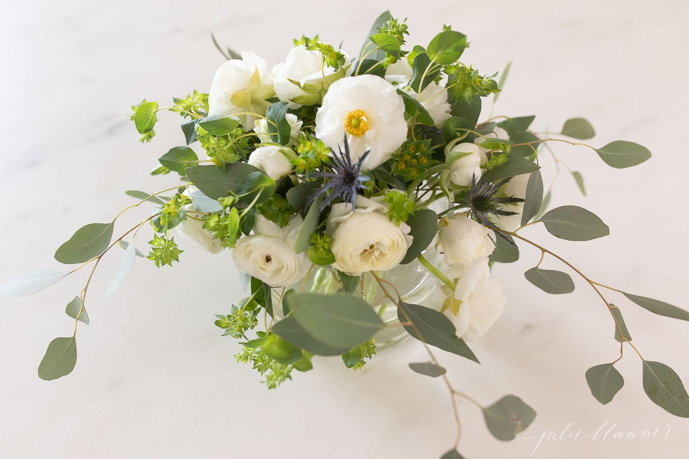 White Ranunulus Centerpiece on a white marble surface.