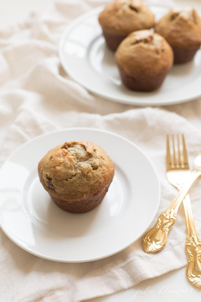 Caramel and Banana Muffin on a white plate, gold silverware to the side.