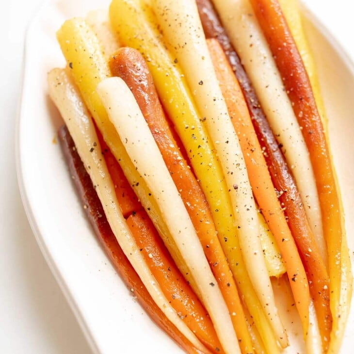 Candied carrots in a white dish.