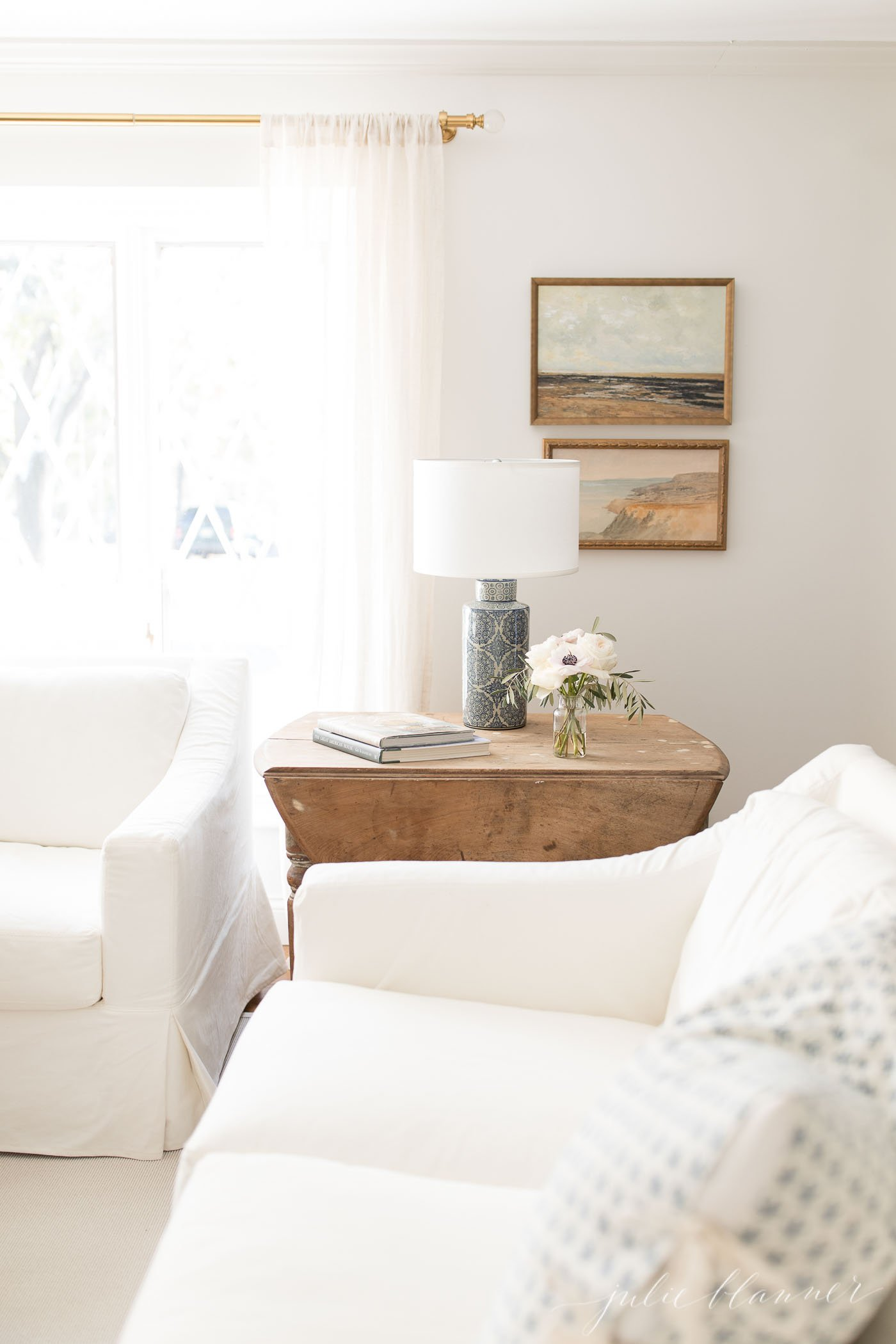 A traditional living room, painted white with white furniture and wood accents, neutral art work