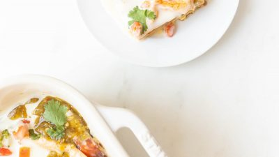 slice of mexican breakfast casserole on a plate next to casserole dish