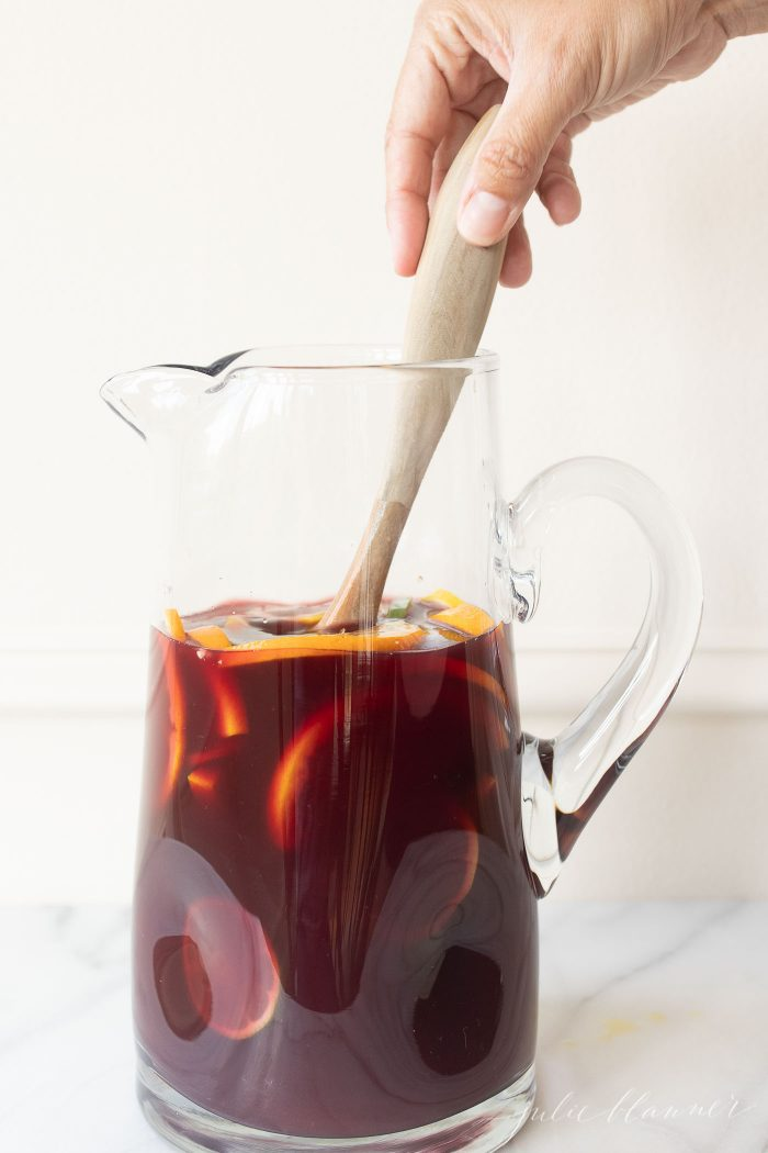 Sangria Punch in a glass pitcher, being mixed with a wooden spoon.