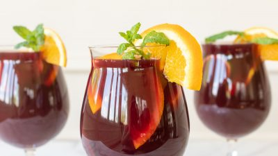 Three cups of sangria, garnished with a lemon slice and mint.