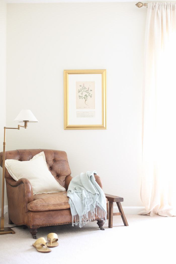 A leather antique chair in a bedroom corner, cream paint on walls and white trim paint.