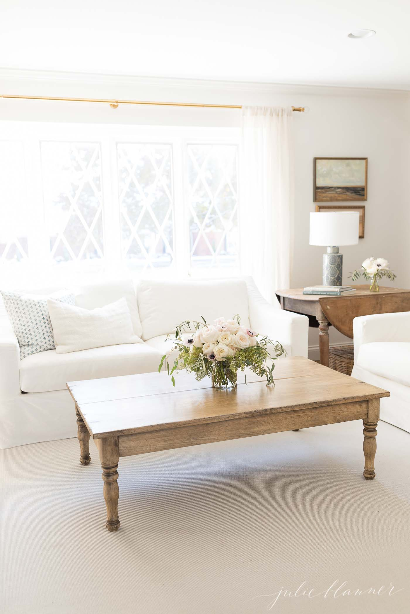 A cream and white living room with a wood coffee table.