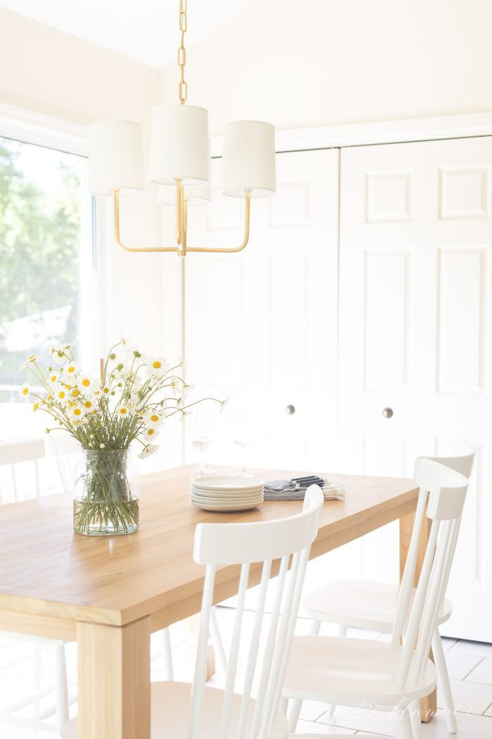 small dining table with white chairs and gold chandelier in eat in kitchen