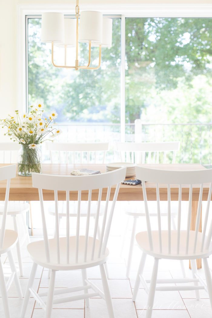 teak table in eat in kitchen with white dining chairs