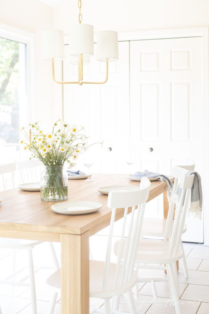 teak dining table in eat in kitchen with flowers and white chairs