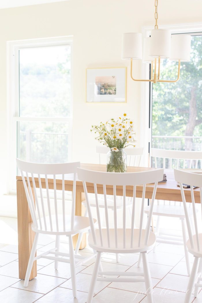 small teak dining table with white chairs
