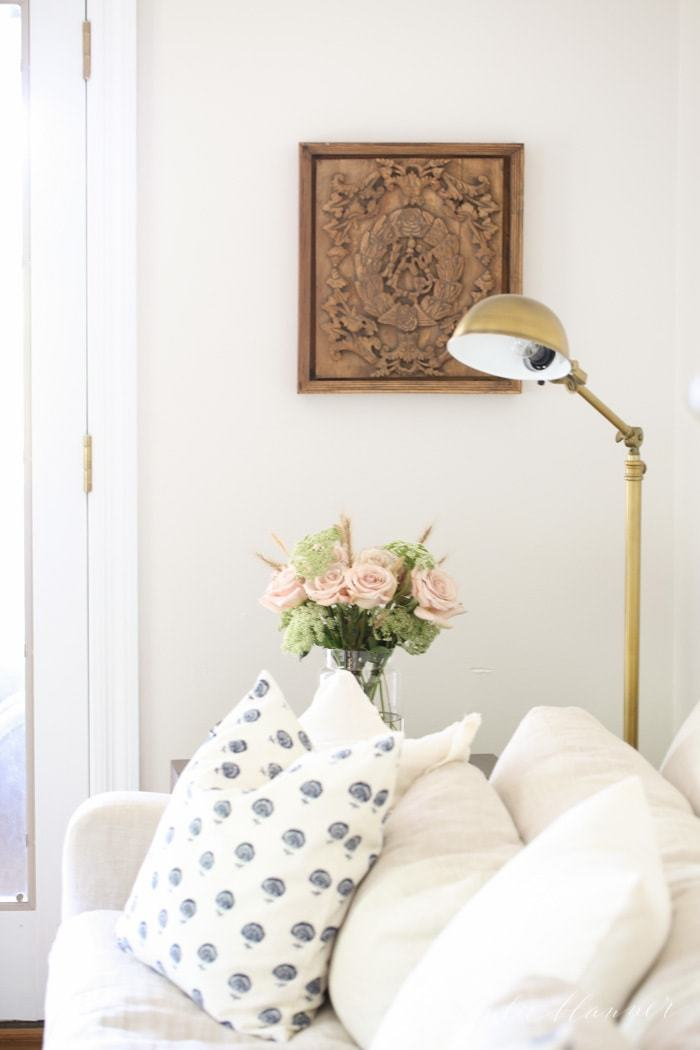 A white living room with a white sofa, wooden art and a brass lamp.