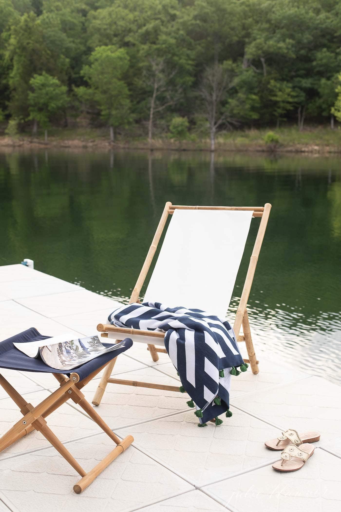 sling chair and folding stool on a dock with lake in background.