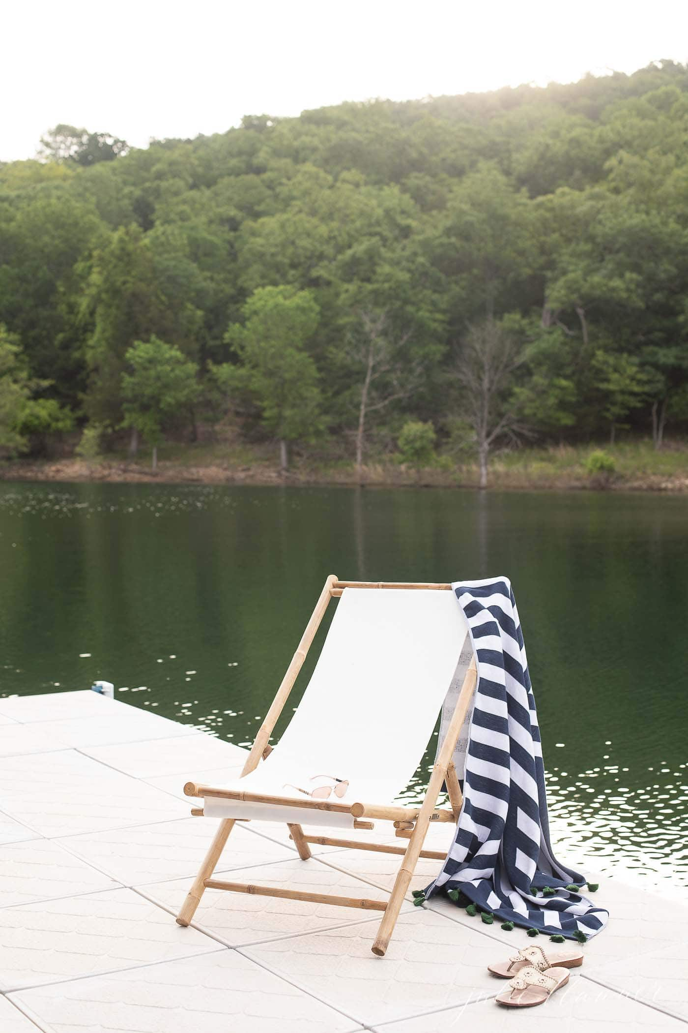 striped beach towel hanging over a folding chair on a dock at a lake.