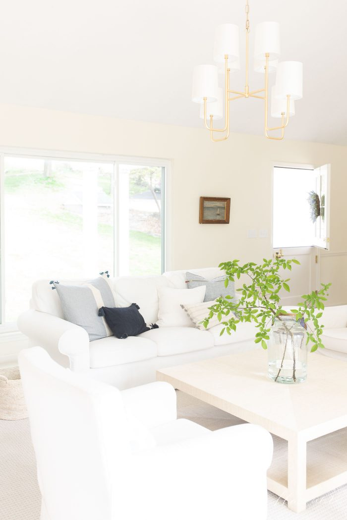 modern living room with white furniture serena and lily pillow covers and a raffia coffee table