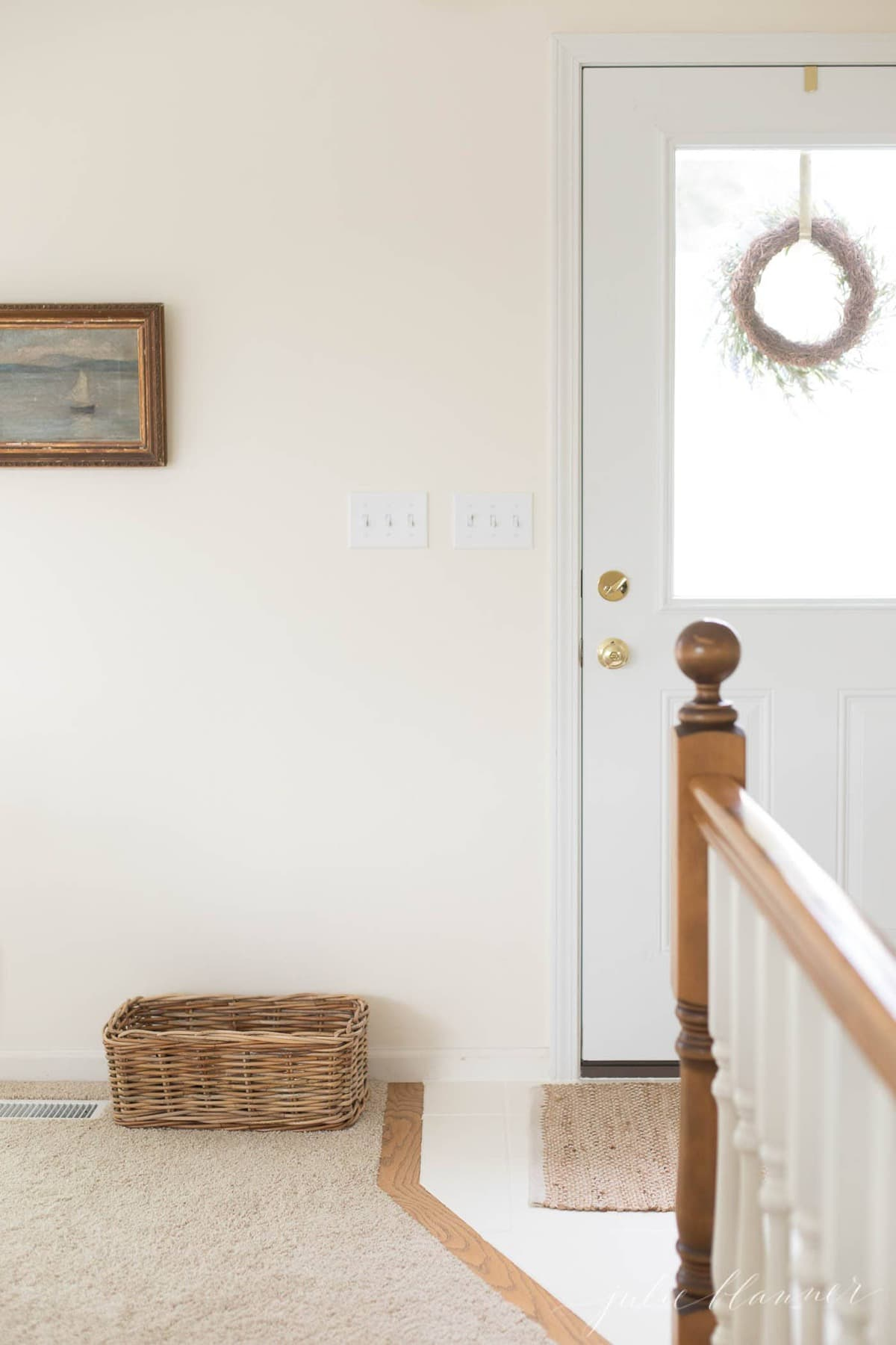 A cream colored entryway with white tile and white trim.