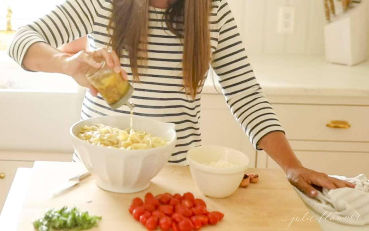 pouring pasta salad dressing onto pasta salad