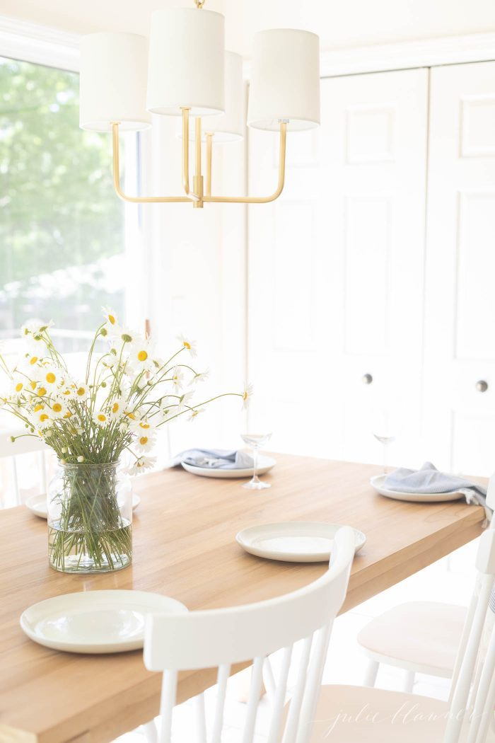 teak table in eat in kitchen with gold chandelier and white chairs