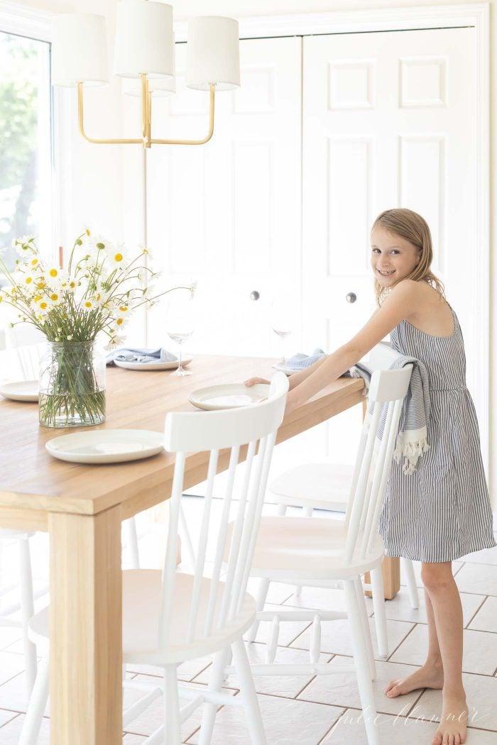 girl setting teak dining table