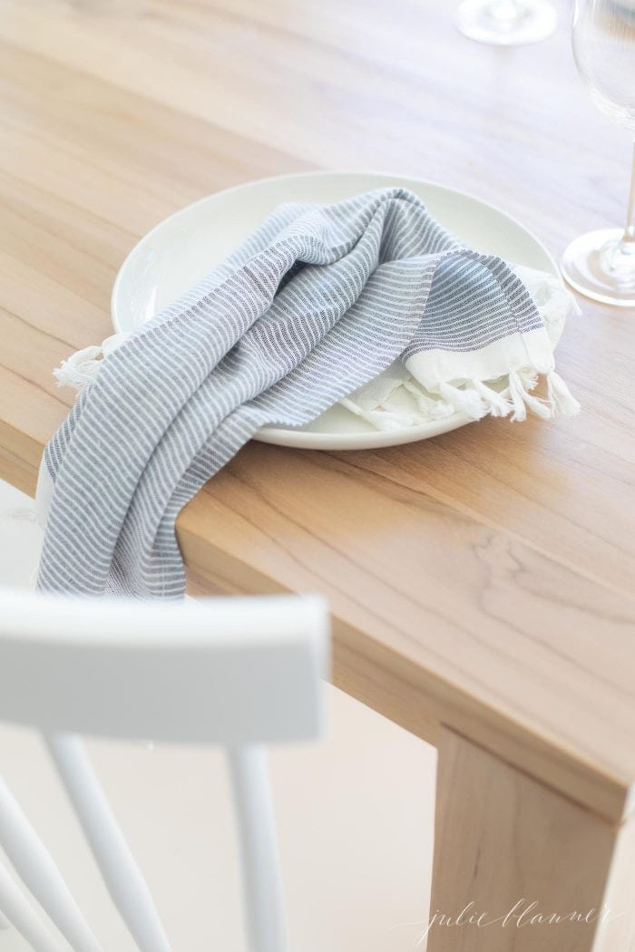 how to give your home a vacation vibe tassel napkins on a teak table