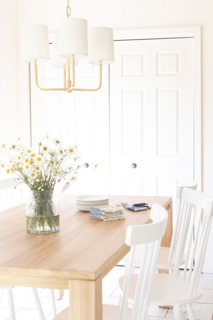 gold chandelier hanging above small dining table in eat in kitchen