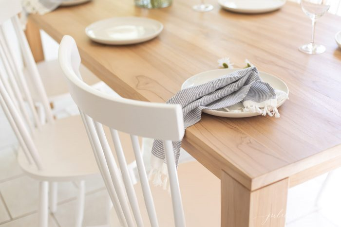 teak dining table with white chairs