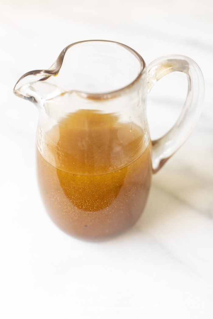 Balsamic vinaigrette in a clear pitcher on a marble surface.