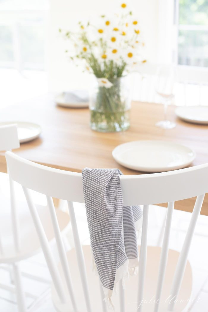 white dining chairs at small dining table with flowers