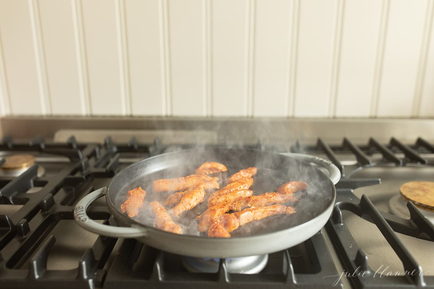 cajun spiced chicken cooking in a cast iron skillet