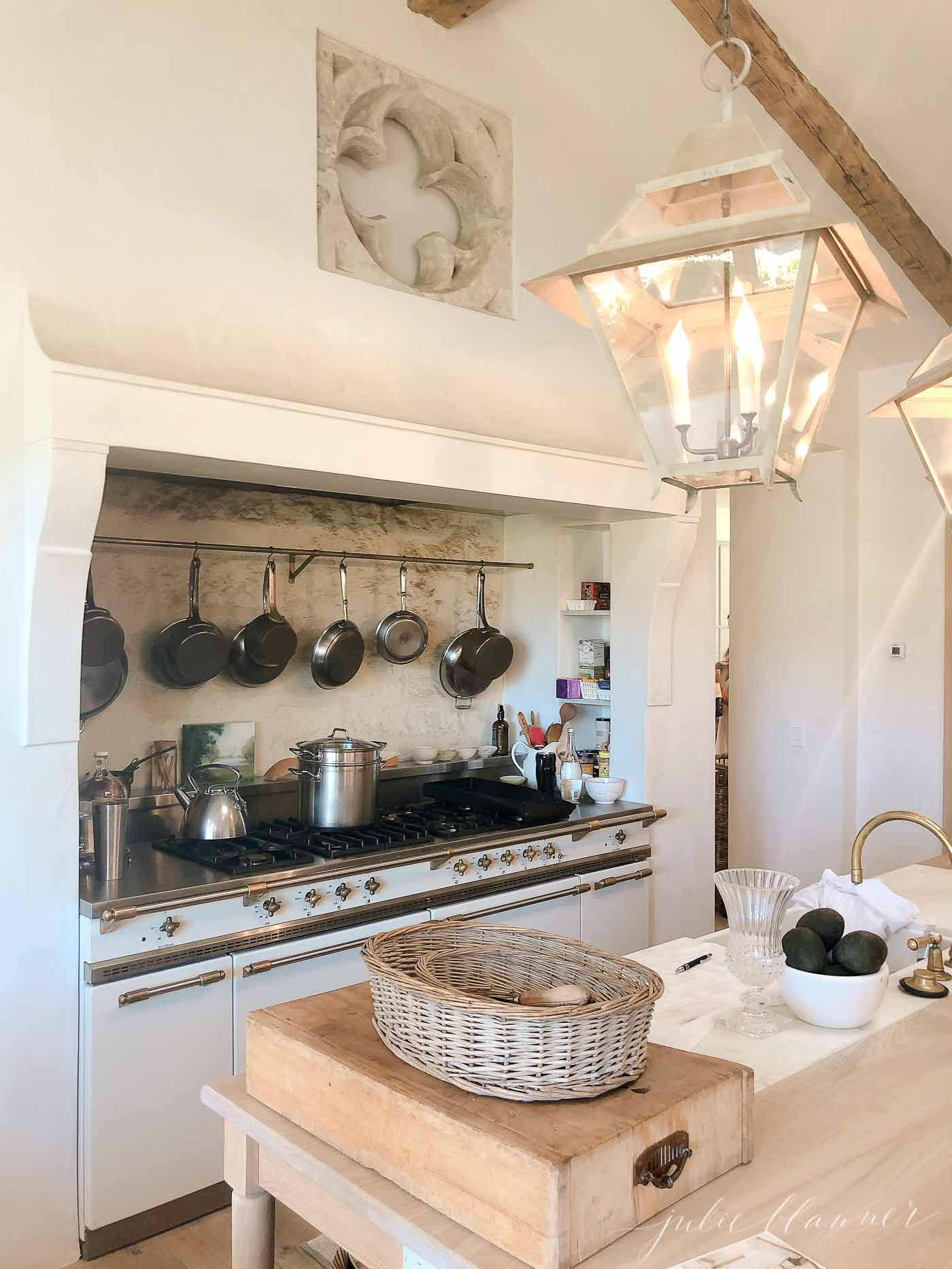 Utilitarian French kitchen with Lacanche range and collection of pots hanging above.