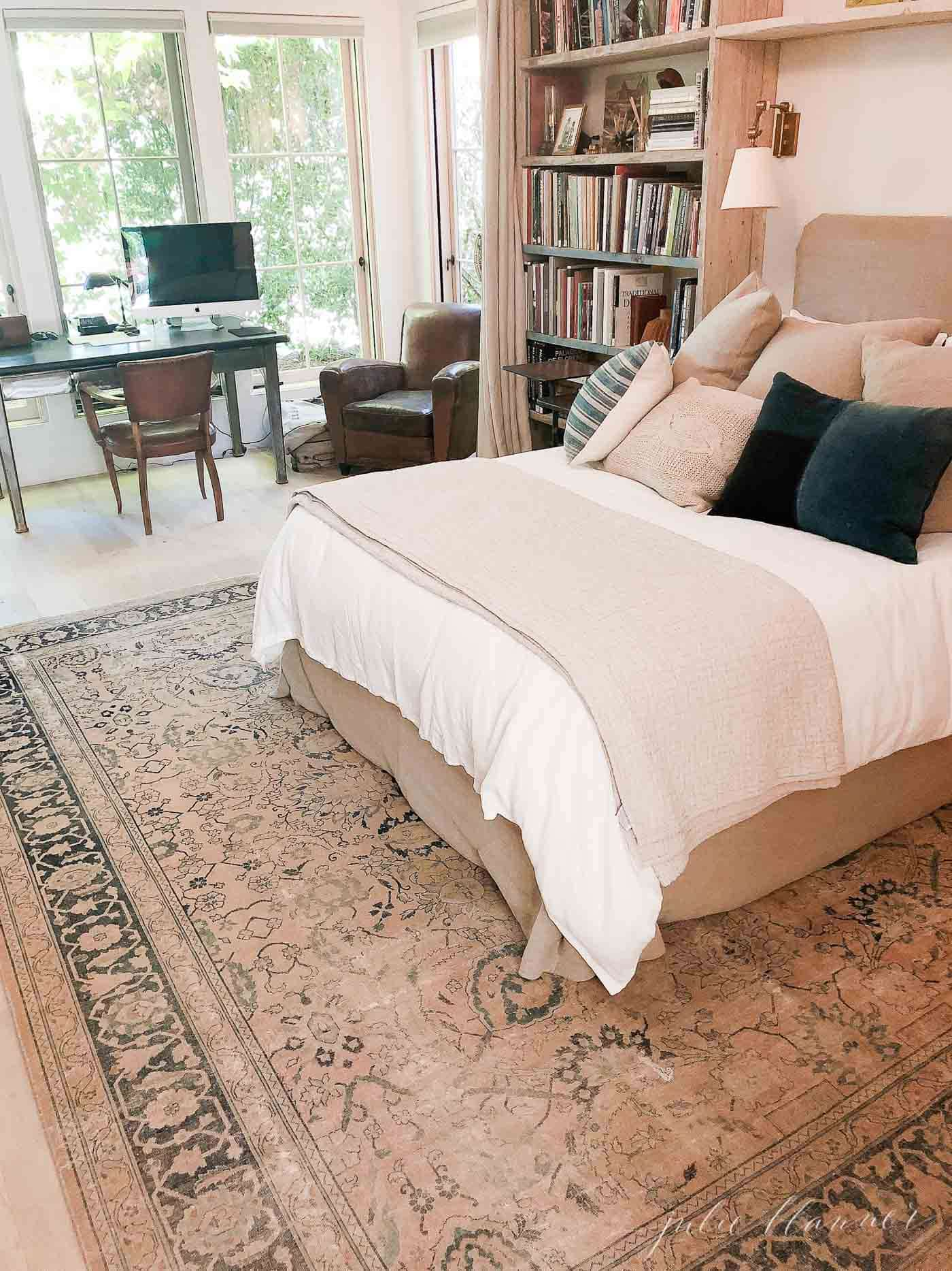 European farmhouse inspired bedroom with antique rug, bookshelves and linen bedding.