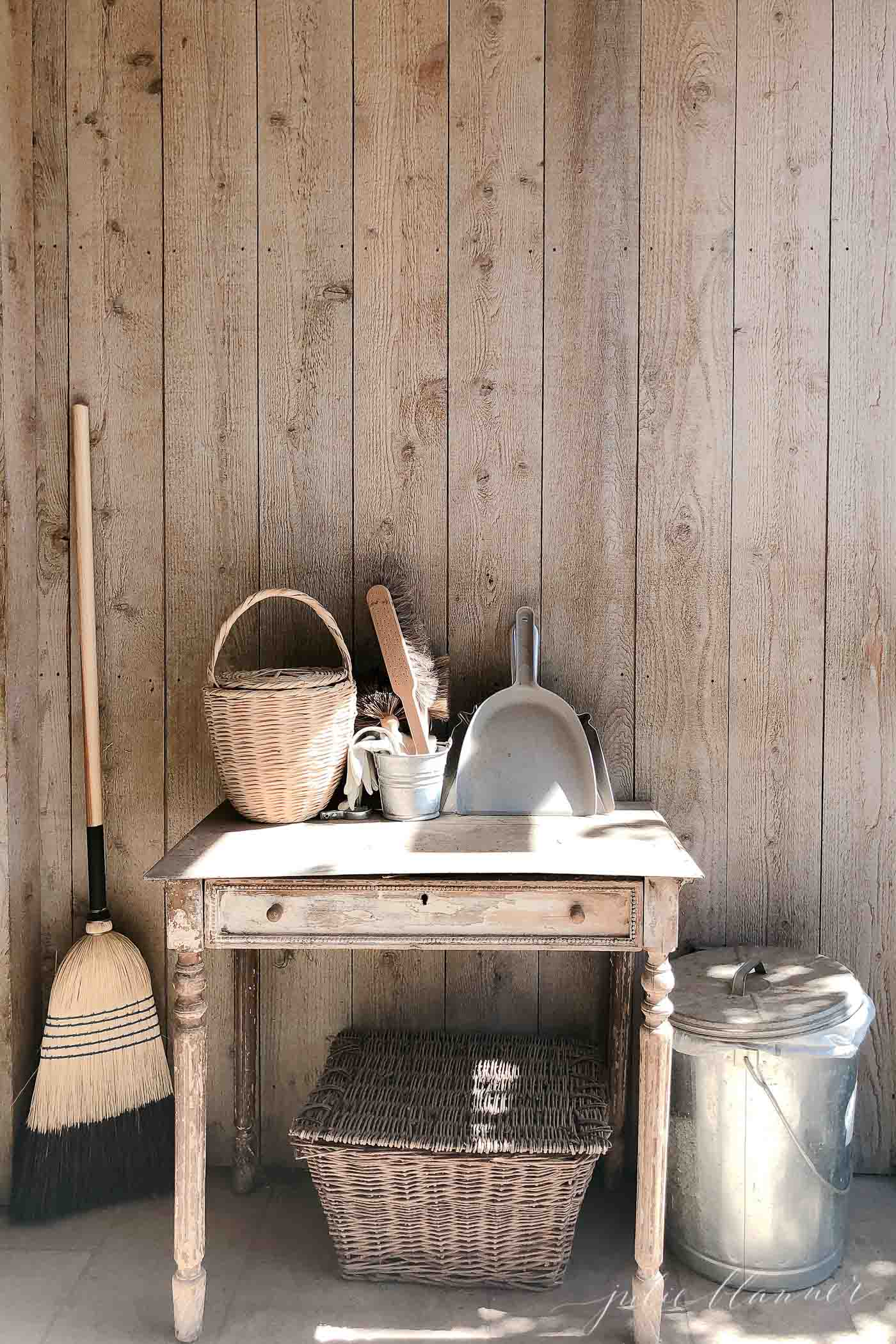 A raw wood wall with a simple wood table, piled with rustic cleaning supplies.