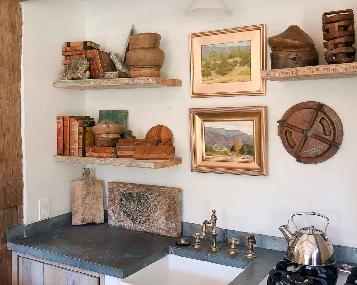 pottery on shelves with art wood beams soapstone counters and farmhouse sink
