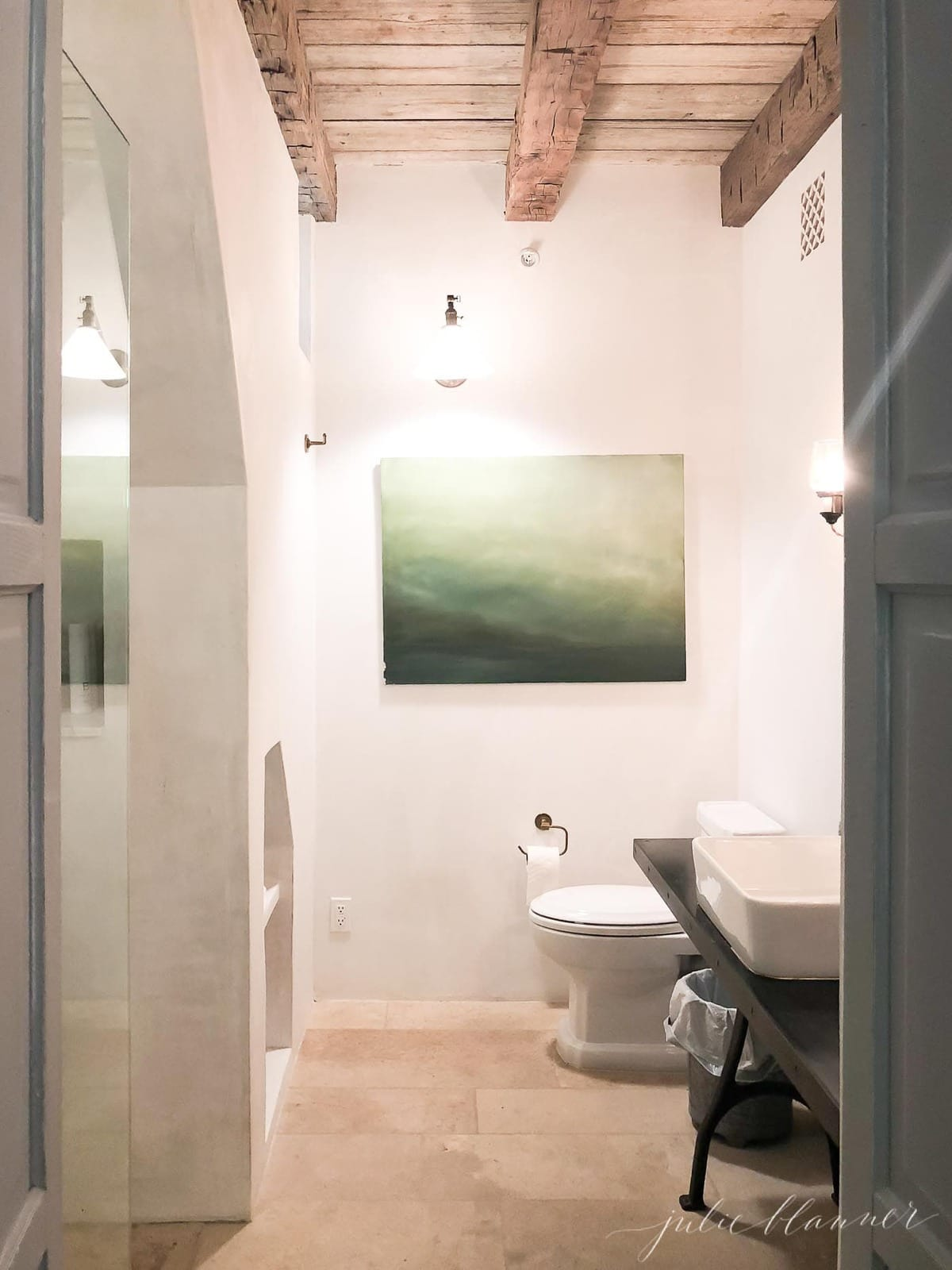 bathroom with wood beams and oversized art