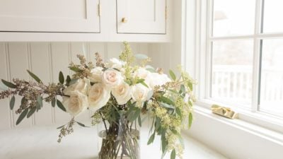 Cream kitchen backdrop with a simple clear cylinder vase filled with roses and eucalytpus.