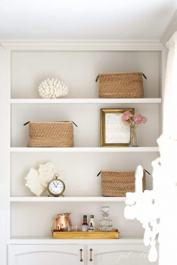 built-in living room shelves with bsakets and simple decor.