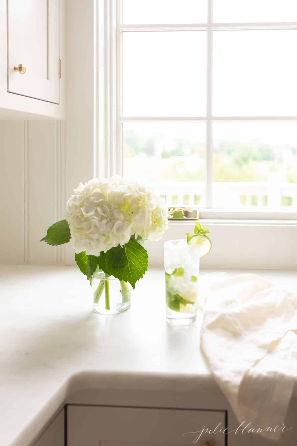 white countertop featuring a vase of hydrangea and a tall clear glass with a mojito.