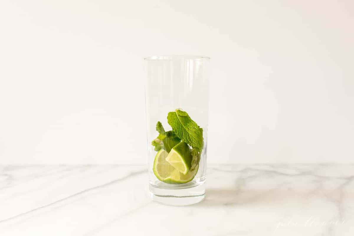 tall drink glass on a marble countertop, with mint and lime at the bottom.
