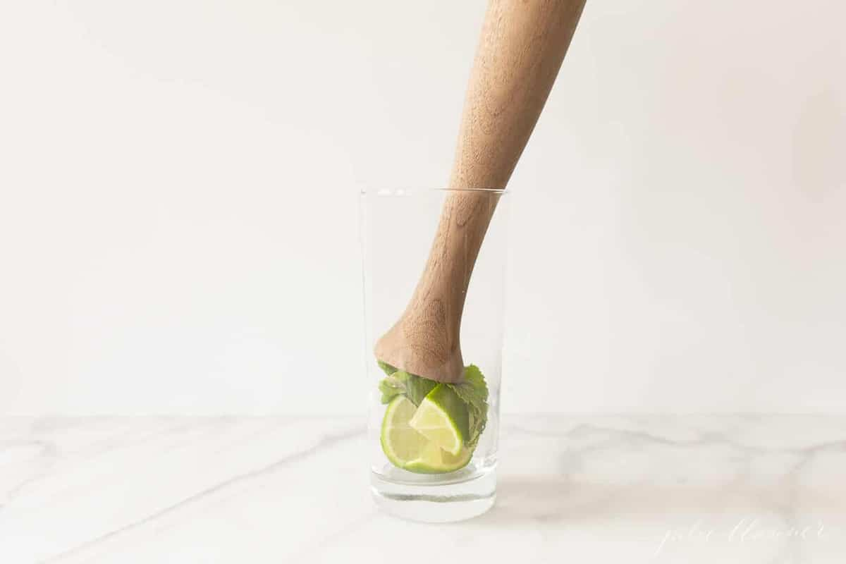 tall glass with a wooden muddler inside, preparing to muddle mint leaves and lime.