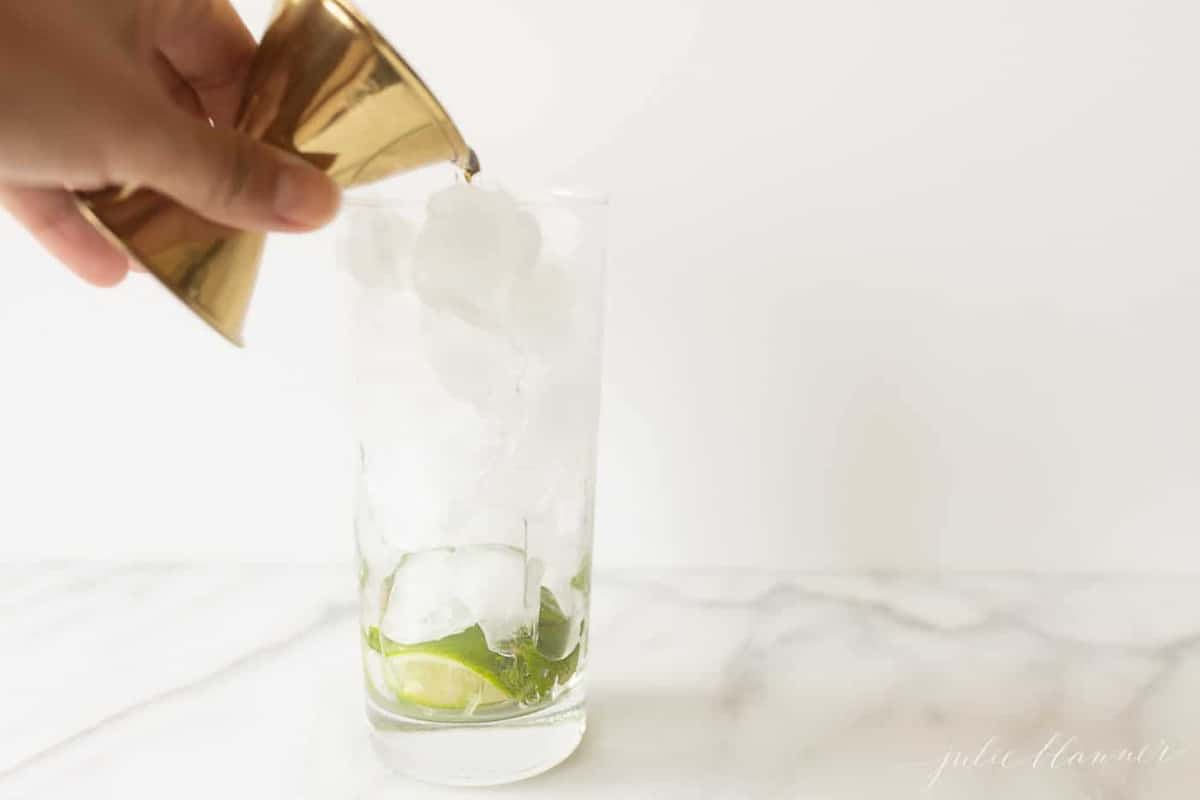 rum pouring into a glass filled with lime, mint and ice.