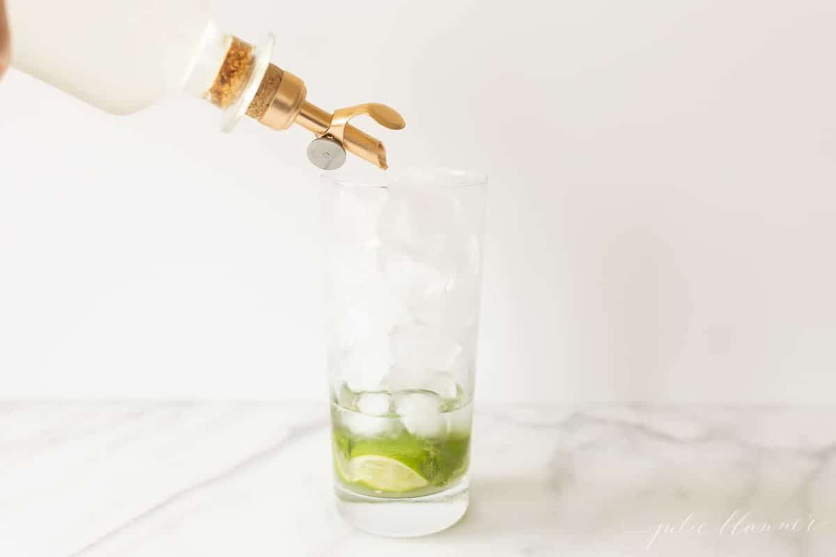 pouring simple syrup into glass to make mojito