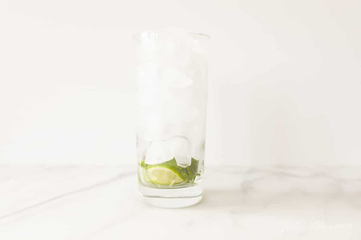 mojito glass with crushed lime and mint filled with ice