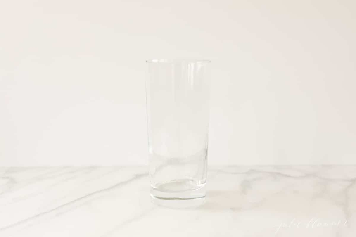 slender clear drink glass on a white marble countertop.