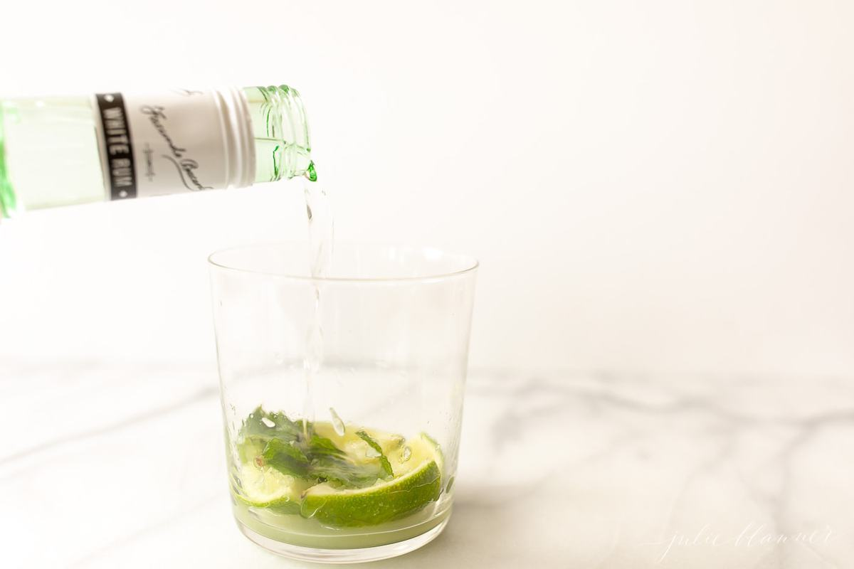 pouring rum over lime and mint in glass